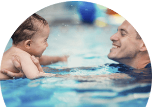 Swim instructor teaching child the front stroke