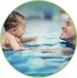 Swim instructor teaching child the front stroke.